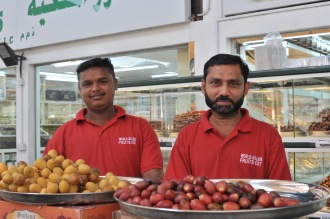 Two Indian men selling crunchy raw dates ready for rippening